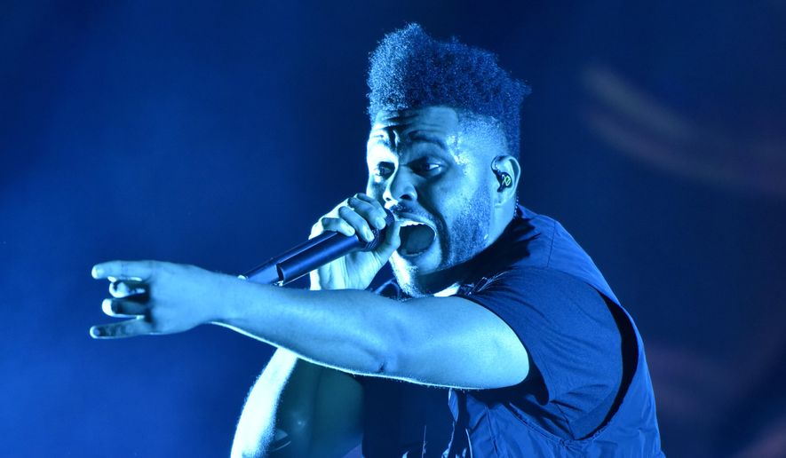 The Weeknd performs on day three at Lollapalooza in Chicago on Aug 4, 2018.  The Weeknd was nominated for eight American Music Awards on Monday. The 2020 American Music Awards will air live on Nov. 22 on ABC. (Photo by Rob Grabowski/Invision/AP, File) **FILE**