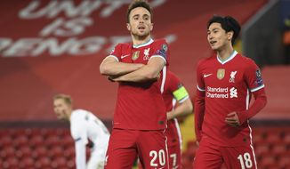 Liverpool's Diogo Jota, 20, celebrates scoring his side's first goal with Liverpool's Takumi Minamino, right, during the Champions League Group D soccer match between Liverpool and FC Midtjylland at Anfield stadium, in Liverpool, England, Tuesday, Oct. 27, 2020. (Michael Regan/Pool via AP)