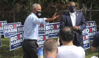Former President Barack Obama waves during a stop at a Biden Victory Center to thank volunteers in Orlando, Fla., Tuesday, Oct. 27, 2020. Earlier in the day, Obama rallied Biden supporters at a drive-in rally at Tinker Field in Orlando. (Joe Burbank/Orlando Sentinel via AP)