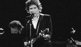 """FILE - Musician Bob Dylan performs with The Band at the Forum in Los Angeles on Feb. 15, 1974. Transcripts of lost 1971 Dylan interviews with the late American blues artist Tony Glover and letters the two exchanged reveal that Dylan changed his name from Robert Zimmerman because he worried about anti-Semitism, and that he wrote """"Lay Lady Lay"""" for actress Barbra Streisand. The items are among a trove of Dylan archives being auctioned in November 2020 by Boston-based R.R. Auction. (AP Photo/Jeff Robbins, File)"""