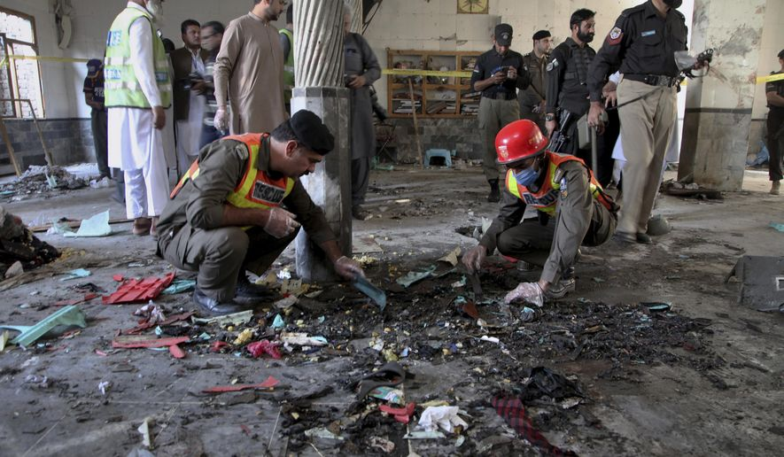 Rescue workers and police officers examine the site of bomb explosion in an Islamic seminary in Peshawar, Pakistan, Tuesday, Oct. 27, 2020. A powerful bomb blast ripped through an Islamic seminary on the outskirts of the northwest Pakistani city of Peshawar on Tuesday morning, killing some students and wounding dozens others, police and a hospital spokesman said. (AP Photo/Muhammad Sajjad)
