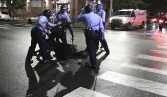 Police surround a man after chasing him down during a violent protest after police shot and killed a 27-year-old Black man on a Philadelphia street early Tuesday, Oct. 27, 2020. (Elizabeth Robertson/The Philadelphia Inquirer via AP)