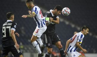 Porto's Otavio jumps for the ball with Olympiacos' Andreas Bouchalakis, center right, during the Champions League group C soccer match between FC Porto and Olympiacos at the Dragao stadium in Porto, Portugal, Tuesday, Oct. 27, 2020. (Miguel Riopa, Pool via AP)