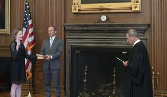 In this image provided by the Collection of the Supreme Court of the United States, Chief Justice John G. Roberts, Jr., right, administers the Judicial Oath to Judge Amy Coney Barrett in the East Conference Room of the Supreme Court Building, Tuesday, Oct. 27, 2020, in Washington as Judge Barrett's husband, Jesse M. Barrett, holds the Bible. (Fred Schilling/Collection of the Supreme Court of the United States via AP)