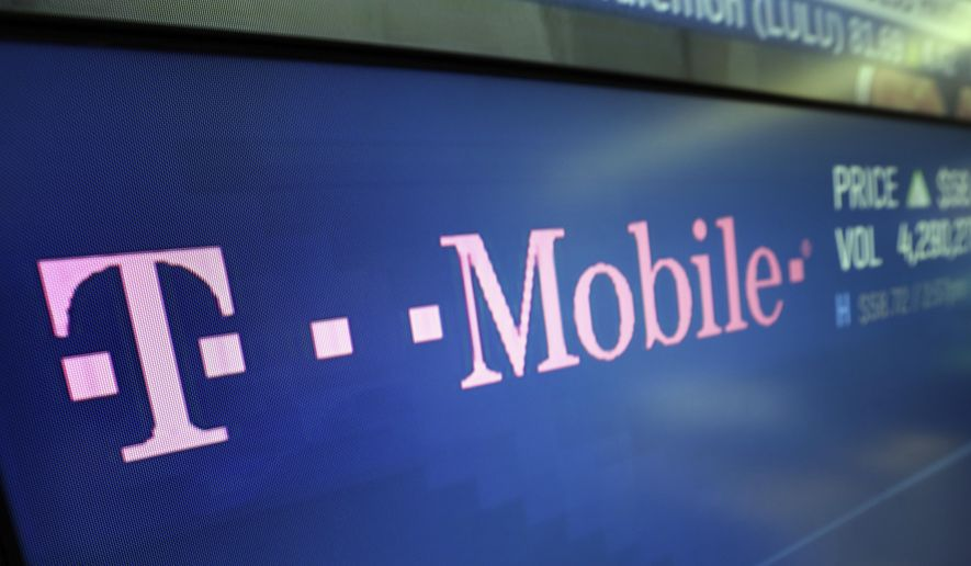 In this Feb. 14, 2018, photo, the T-Mobile logo appears on a screen at the Nasdaq MarketSite in New York. (AP Photo/Richard Drew) **FILE**