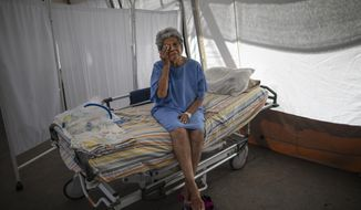 Nancy Rodriguez, a 76-yar-old COVID-19 patient, wipes tears as she explains her battle with the virus under a tent for patients who will be discharged from the Peréz de León II Hospital, a public hospital where Doctors Without Borders operates in the Petare neighborhood of Caracas, Venezuela, Monday, Sept. 22, 2020. Venezuela's count of roughly 800 COVID-19 deaths among its more than 90,000 cases is likely an undercount, as many are fearful of the broken health care system and choose to stay home. (AP Photo/Ariana Cubillos)