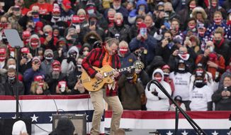 Musician Ted Nugent plays the national anthem before a President Donald Trump campaign event, Tuesday, Oct. 27, 2020, in Lansing, Mich. (AP Photo/Carlos Osorio)