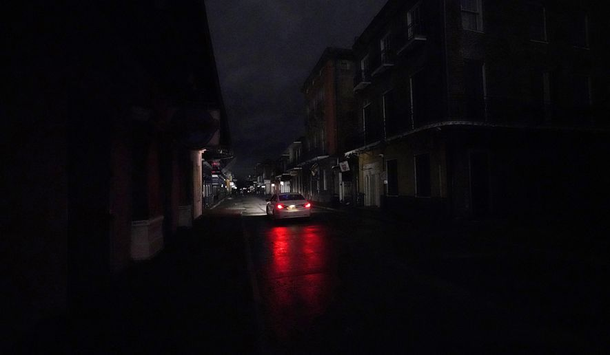 A passing car's headlights illuminate a darkened Bourbon Street in the French Quarter of New Orleans, Wednesday, Oct. 28, 2020. Hurricane Zeta passed through Wednesday leaving much of the city and metro area without power. (AP Photo/Gerald Herbert)