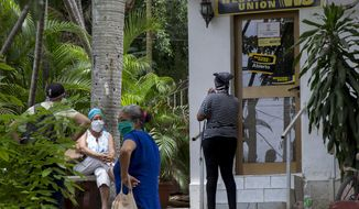 FILE - In this June 12, 2020 file photo, people stand outside a Western Union in the Vedado neighborhood of Havana, Cuba. The Cuban Government announced Tuesday, Oct. 27, 2020, it will move to close over 400 Western Union offices around the island because of a new Trump Administration sanction prohibiting a government agency from handling the financial transactions allowing Cuban citizens to receive dollar remittances from relatives abroad. The closures potentially could affect millions of residents who rely on the money relatives send to make ends meet. (AP Photo/Ismael Francisco, File)
