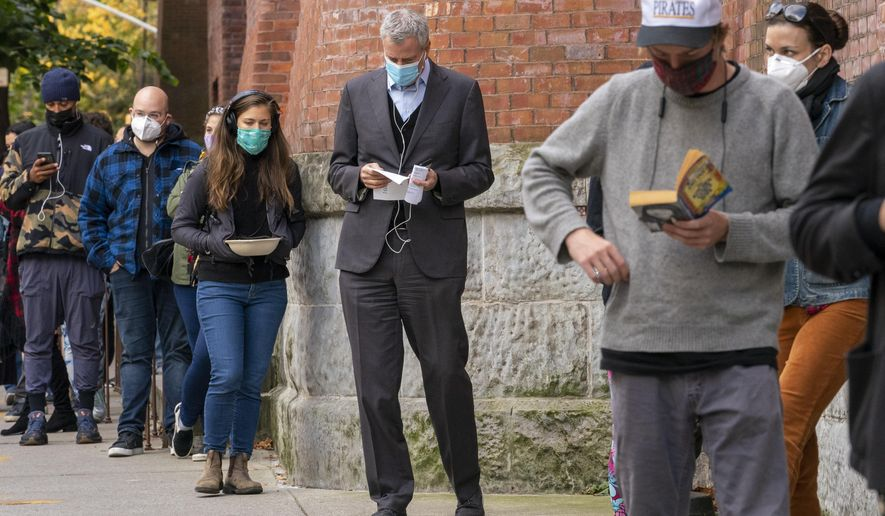 New York Mayor Bill de Blasio, center, stands in line to cast his early vote at the Park Slope Armory YMCA, Tuesday, Oct. 27, 2020, in the Brooklyn borough of New York. The mayor waited over three hours in line to cast his vote. (AP Photo/Mary Altaffer)