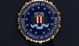 FILE - This Thursday, June 14, 2018, file photo, shows the FBI seal at a news conference at FBI headquarters in Washington. In an alert Wednesday, Oct. 28, 2020, the FBI and other federal agencies warned that cybercriminals are unleashing a wave of data-scrambling extortion attempts against the U.S. healthcare system that could lock up their information systems just as nationwide cases of COVID-19 are spiking. (AP Photo/Jose Luis Magana, File)