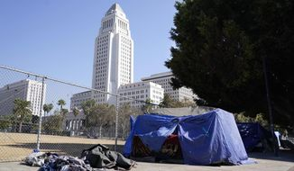 A homeless person's tent stands just outside Grand Park with Los Angeles City Hall in the background, Wednesday, Oct. 28, 2020, in Los Angeles. Los Angeles is again considering a proposal to greatly restrict where homeless people may camp in public places around Los Angeles - rules that opponents say would criminalize homelessness. (AP Photo/Chris Pizzello)