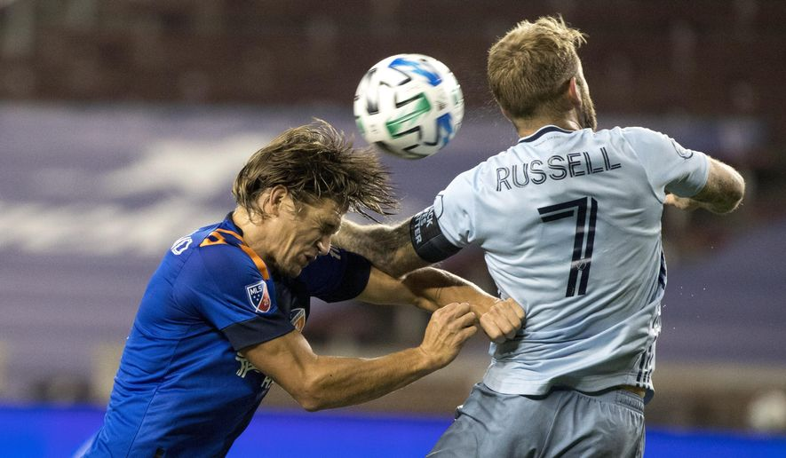 FC Cincinnati defender Nick Hagglund (14) heads the ball as Sporting Kansas City forward Johnny Russell (7) defends during the first half of an MLS soccer match Wednesday, Oct. 28, 2020, in Cincinnati. (Albert Cesare/The Cincinnati Enquirer via AP)