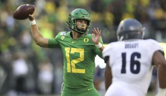 FILE - In this Sept. 7, 2019, file photo, Oregon quarterback Tyler Shough, left, throws a pass against Nevada during the third quarter of an NCAA college football game in Eugene, Ore. Expected to finish atop the Pac-12, the Ducks open at home with Stanford. The rivalry game against Oregon State will still be Thanksgiving weekend. (AP Photo/Chris Pietsch, File)