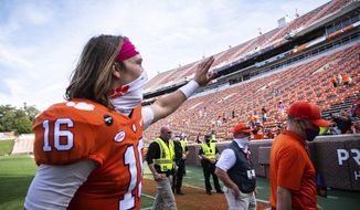 Clemson quarterback Trevor Lawrence (16) waves to fans after an NCAA college football game against Syracuse in Clemson, S.C., on Saturday, Oct. 24, 2020. (Ken Ruinard/Pool Photo via AP)
