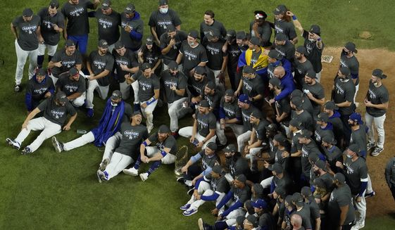 Los Angeles Dodgers pose for a group picture after defeating the Tampa Bay Rays 3-1 to win the baseball World Series in Game 6 Tuesday, Oct. 27, 2020, in Arlington, Texas. (AP Photo/David J. Phillip)  **FILE**