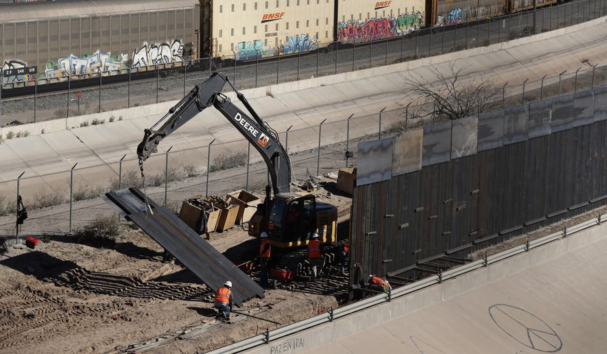 Workers place sections of metal wall as a new barrier is built along the Texas-Mexico border Tuesday, Jan. 22, 2019, near downtown El Paso. Top Trump administration officials will visit South Texas five days before Election Day to announce they have completed 400 miles of U.S.-Mexico border wall, attempting to show progress on perhaps the president's best-known campaign promise four years ago. But most of the wall went up in areas that already had smaller barriers. (AP Photo/Eric Gay) **FILE**
