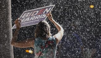 A supporter stands in the rain as Democratic presidential candidate former Vice President Joe Biden speaks at a drive-in rally at the Florida State Fairgrounds, Thursday, Oct. 29, 2020, in Tampa, Fla. (AP Photo/Andrew Harnik)