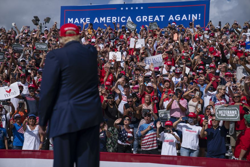Supporters cheer as President Donald Trump arrives for a campaign rally outside Raymond James Stadium, Thursday, Oct. 29, 2020, in Tampa. (AP Photo/Evan Vucci)