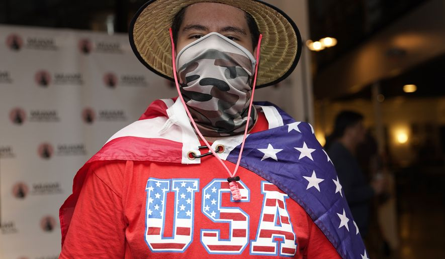 In this Sept. 29, 2020, file photo, Eddie Collantes stands with an American flag draped around his shoulders as he attends a debate watch party hosted by the Miami Young Republicans, Latinos for Trump, and other groups in Miami. (AP Photo/Lynne Sladky, File)