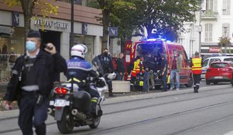 French policemen and firemen stand next to Notre Dame church after a knife attack, in Nice, France, Thursday, Oct. 29, 2020. French anti-terrorism prosecutors are investigating a knife attack at a church in the Mediterranean city of Nice that killed two people and injured several others. (AP Photo/Alexis Gilli)