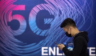 """A man looks at his smartphone as he walks past a sign advertising 5G services at the PT Expo in Beijing, Wednesday, Sept. 14, 2020. China's leaders vowed Thursday, Oct. 29, 2020, to speed up its development as a self-reliant """"technology power"""" amid a feud with Washington that is cutting access to U.S. components and hampering Beijing's industrial ambitions. (AP Photo/Mark Schiefelbein)"""