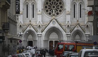French policemen and forensic officers stand in front of Notre Dame church after a knife attack, in Nice, France, Thursday, Oct. 29, 2020. French anti-terrorism prosecutors are investigating a knife attack at a church in the Mediterranean city of Nice that killed two people and injured several others. (AP Photo/Daniel Cole)