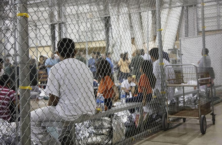 In this June 17, 2018, file photo provided by U.S. Customs and Border Protection, people who've been taken into custody related to cases of illegal entry into the United States, sit in one of the cages at a facility in McAllen, Texas. A federal judge on Thursday, Oct. 22, 2020, urged the Trump administration to do more to help court-appointed researchers find hundreds of parents who were separated from their children after they crossed the U.S.-Mexico border beginning in 2017. (U.S. Customs and Border Protection's Rio Grande Valley Sector via AP, File)