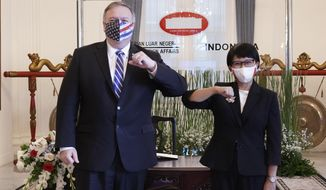 In this photo released by Indonesian Ministry of Foreign Affairs, U.S. Secretary of State Mike Pompeo, left, and Indonesian Foreign Minister Retno Marsudi pose for photographers during their meeting in Jakarta, Indonesia, Thursday, Oct. 29, 2020. Pompeo renewed the Trump administration's rhetorical onslaught against China in Indonesia on Thursday as the American presidential election looms. (Indonesian Ministry of Foreign Affairs via AP)