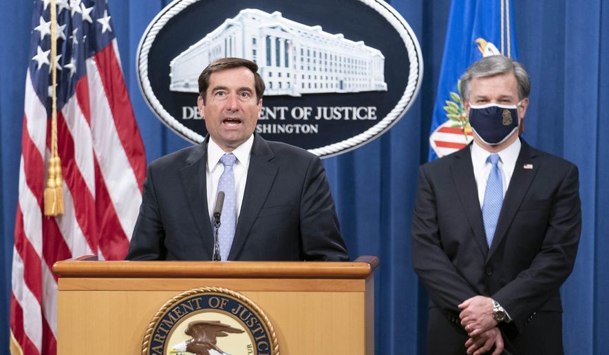 Assistant Attorney General for National Security John Demers speaks during a virtual news conference at the Department of Justice, Wednesday, Oct. 28, 2020, in Washington, as FBI Director Christopher Wray looks on. (Sarah Silbiger/Pool via AP) ** FILE **