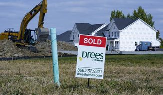 "A ""sold"" sign sits on a lot as new home construction continues in Westfield, Ind., Friday, Sept. 25, 2020.  U.S. long-term mortgage rates were little changed this week of Oct. 29, after marking a new all-time low last week. Home loan rates have declined through the year amid economic anxiety in the recession set off by the coronavirus pandemic.  (AP Photo/Michael Conroy)"