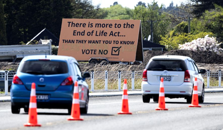 """FILE - In this Oct. 16, 2020, file photo, cars are driven past a billboard urging voters to vote """"No"""" against euthanasia in Christchurch, New Zealand. New Zealanders have voted on Friday, Oct. 30, 2020 in favor of legalizing euthanasia in a binding referendum. But in preliminary results they were rejecting a measure to legalize marijuana. (AP Photo/Mark Baker, File)"""