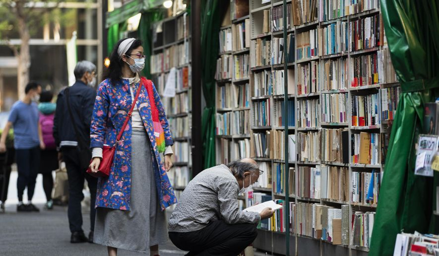 People wearing face masks shop around at a secondhand book store in Tokyo on Thursday, Oct. 29, 2020. (AP Photo/Hiro Komae)