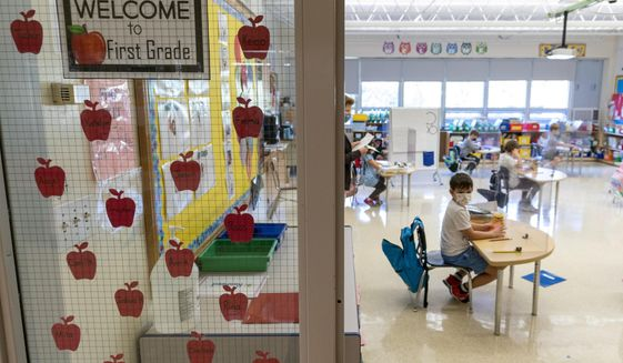 First grade students sit at their desks set up for proper social distancing during the coronavirus outbreak at the Osborn School, Tuesday, Oct. 6, 2020, in Rye, N.Y. (AP Photo/Mary Altaffer)