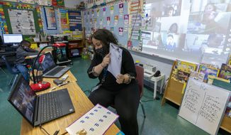 First grade teacher Megan Garner-Jones teaches students participating remotely and in person during the coronavirus outbreak at School 16, Tuesday, Oct. 20, 2020, in Yonkers, N.Y. (AP Photo/Mary Altaffer)   **FILE**