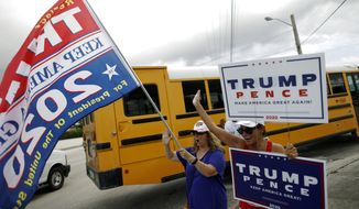Supporters of President Donald Trump hold signs and wave to passing cars, outside an early voting polling station in Lake Worth, Fla., Friday, Oct. 30, 2020.(AP Photo/Rebecca Blackwell)