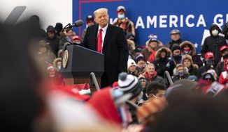 President Donald Trump watches a video as he speaks at a campaign rally at Oakland County International Airport, Friday, Oct. 30, 2020, at Waterford Township, Mich. (AP Photo/Alex Brandon)