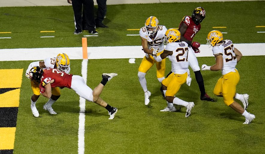 Maryland running back Jake Funk (34) dives in for a touchdown against Minnesota defensive back Jordan Howden (23) during the second half of an NCAA college football game, Friday, Oct. 30, 2020, in College Park, Md. Maryland won 45-44 in overtime. (AP Photo/Julio Cortez) **FILE**