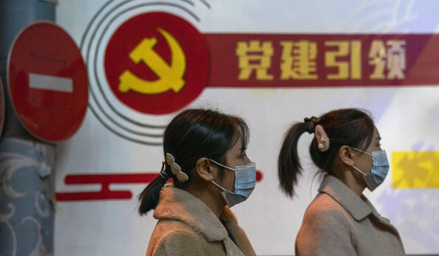 "Residents wearing masks pass by the Communist party logo and the slogan ""Party building leadership"" in Beijing on Thursday, Oct. 29, 2020. China will promote ""technological self-reliance"" under the ruling Communist Party's latest five-year plan but will open further to trade, officials said Friday. (AP Photo/Ng Han Guan) **FILE**"