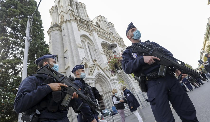French police officers stand near Notre Dame church in Nice, southern France, Thursday, Oct. 29, 2020. French President Emmanuel Macron has announced that he will more than double number of soldiers deployed to protect against attacks to 7,000 after three people were killed at a church Thursday. (Eric Gaillard/Pool via AP)