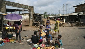 A woman sits next her goods to sale on a street market in Bonoua, in the outskirts of Abidjan, Ivory Coast, Friday, Oct. 30, 2020. Opposition activists are threatening to block access to polling stations Saturday in an effort to disrupt the presidential election in Ivory Coast, where incumbent Alassane Ouattara is seeking a controversial third term after nearly a decade in power. (AP Photo/Leo Correa)