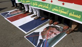 Supporters of the Muslims Students Organization stand on a representation of a French national flag and defaced images of French President Emmanuel Macron during a protest against the president and against the publishing of caricatures of the Prophet Muhammad they deem blasphemous, in Karachi, Pakistan, Friday, Oct. 30, 2020. Muslims have been calling for both protests and a boycott of French goods in response to France's stance on caricatures of Islam's most revered prophet. (AP Photo/Fareed Khan)