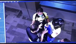 This image made from the Oct. 2, 2020, surveillance camera footage obtained by the website Doha News shows officials care for an abandoned baby at Hamad International Airport in Doha, Qatar. Qatar apologized Wednesday, Oct. 28, 2020, after authorities forcibly examined female passengers from a Qatar Airways flight to Sydney to try to identify who might have given birth to the abandoned newborn baby, even as Australia said it was only one of 10 flights subjected to the searches. (Doha News via AP)
