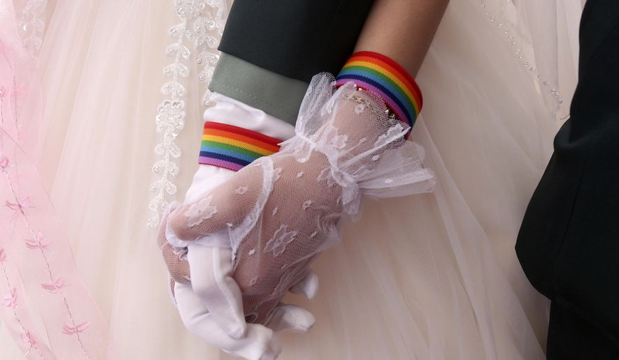 In this file photo, Chen Ying-hsuan, right, holds Li Li-chen's hand during a military mass weddings ceremony in Taoyuan city, northern Taiwan, Friday, Oct. 30, 2020. Two lesbian couples tied the knot in a mass ceremony held by Taiwan's military on Friday in a historic step for the island. (AP Photo/Chiang Ying-ying)  **FILE**