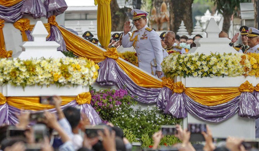 King Maha Vajiralongkorn, center, waves as he arrives to participate in a graduation ceremony at Thammasat University in Bangkok, Thailand, Friday, Oct. 30, 2020. (AP Photo/Sakchai Lalit)