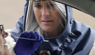 FILE - In this Friday, Oct. 23, 2020 file photo, Salt Lake County Health Department public health nurse Lee Cherie Booth performs a coronavirus test outside the Salt Lake County Health Department in Salt Lake City. Utah Gov. Gary Herbert and health officials issued repeated pleas for social distancing and mask usage on Thursday, Oct. 29, 2020, as hospitals grow closer to implementing crisis care protocols amid a record-breaking coronavirus surge. (AP Photo/Rick Bowmer, File)