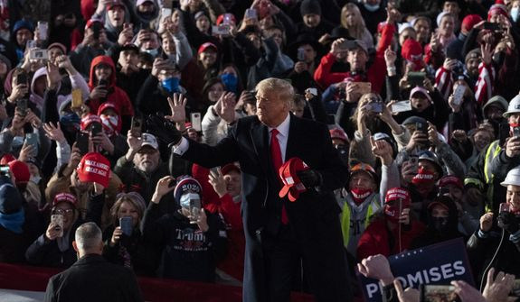 President Donald Trump throws a hat to supporters before he speaks at a campaign rally at Pittsburgh-Butler Regional Airport, Saturday, Oct. 31, 2020, in Butler, Pa. (AP Photo/Alex Brandon)