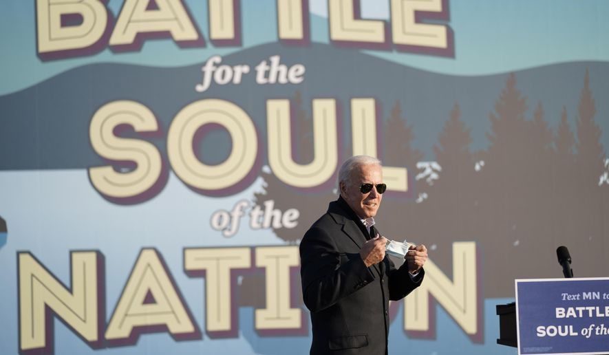 Democratic presidential candidate former Vice President Joe Biden holds his face mask during a rally at the Minnesota State Fairgrounds in St. Paul, Minn., Friday, Oct. 30, 2020. (AP Photo/Andrew Harnik)