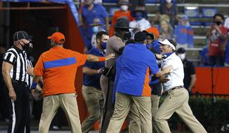 Florida coach Dan Mullen, right, is held back by coaches and law enforcement after a fight broke out at the end of the first half of the team's NCAA college football game against Missouri in Gainesville, Fla., Saturday, Oct. 31, 2020. (Brad McClenny/The Gainesville Sun via AP) **FILE**