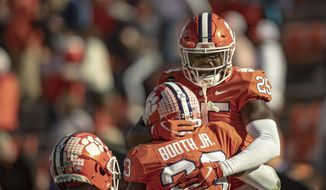 Clemson safety Jalyn Phillips (25) celebrates a defensive stop with cornerback Andrew Booth Jr. (23) during the second half of an NCAA college football game  Saturday, Oct. 31, 2020, in Clemson, S.C. (Josh Morgan/Pool Photo via AP)  **FILE**